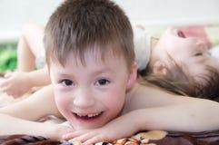 Skratta för ungar, lyckliga barn som ler ståenden som tillsammans spelar syskon, lilla flickan och pojken, syskongrupp Royaltyfri Bild