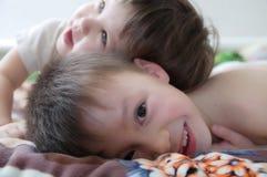 Skratta för ungar, lyckliga barn som ler ståenden som tillsammans spelar syskon, lilla flickan och pojken, syskongrupp Arkivfoton
