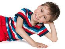 Skratta förskole- vila för pojke Arkivfoto