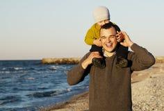 Skratta fadern som ger hans sonny en ridtur på axlarna Arkivbild