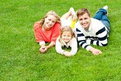 Skratta familj av tre som har gyckel tillsammans Arkivbild