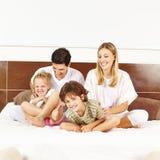 Skratta familjen med barn på säng Royaltyfria Foton