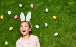 Skratta flickan med kulöra ägg i äng royaltyfri foto