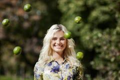 Skratta flickan med limefrukter parkera in Royaltyfria Bilder