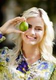 Skratta flickan med limefrukter parkera in Arkivbild