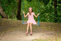 Skratta flickan på ett träd svänger Arkivfoto