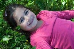 Skratta flickan som ligger på gräset Fotografering för Bildbyråer