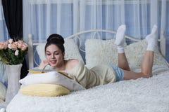 Skratta flickan som ligger på sängen och läsningen en bok Royaltyfria Foton