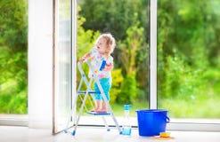 Skratta flickan som tvättar ett fönster royaltyfria foton