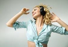 Skratta flickan som tycker om den realaxing musiken Arkivbilder