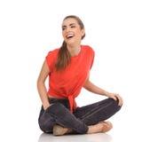 Skratta flickasammanträde på golvet med korsade ben Royaltyfria Foton