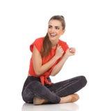 Skratta flickasammanträde på golvet med korsade ben Royaltyfri Foto