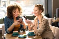 Skratta flickor som håller ögonen på på mobiltelefoner Royaltyfria Bilder
