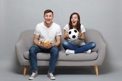 Skratta fotbollsfan för parkvinnamannen hurra upp det favorit- laget för service med fotbollbollen som rymmer exponeringsglasbunk royaltyfri fotografi
