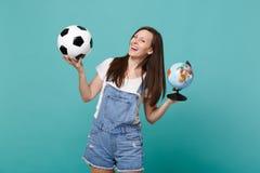 Skratta fotbollsfanjubel för ung kvinna upp det favorit- laget för service med fotbollbollen, världsjordklot som isoleras på blåt arkivbild