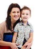 Skratta framsidor av modern och henne son Arkivfoto
