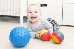 Skratta 6 gulliga månad behandla som ett barn flickalekbollar Royaltyfri Bild