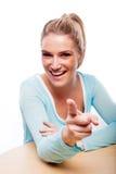 Skratta härligt blont peka hennes finger Royaltyfri Foto