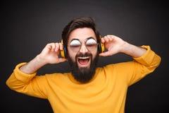 Skratta hipstermannen som lyssnar till musik royaltyfri foto