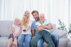 Skratta hållande ögonen på TV för familj tillsammans Royaltyfria Foton