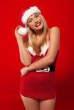 Skratta kvinna i en Santa dräkt Arkivbild