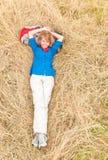 Skratta kvinna som ner ligger på gräs i äng. Arkivbilder