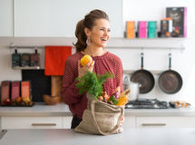 Skratta kvinnan i profil, nedgångfrukt och grönsaker i kök Arkivfoton
