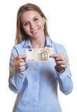 Skratta kvinnan med anmärkningen för euro 50 i hennes hand Arkivfoto