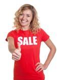 Skratta kvinnan med blont hår i en tumme för försäljningsskjortavisning Royaltyfri Fotografi