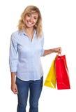 Skratta kvinnan med lockigt blont hår och två shoppingpåsar Royaltyfri Fotografi