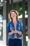 Skratta kvinnan med telefonen och hörlurar som går i stad royaltyfria foton