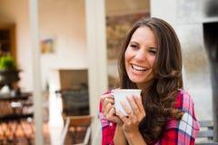 Skratta kvinnan som dricker kaffe Arkivfoto