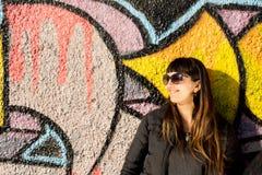 Skratta kvinnan som poserar på färgglade grafitti Royaltyfri Fotografi