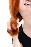 Skratta kvinnan som rullar ihop hennes röda hår Fotografering för Bildbyråer