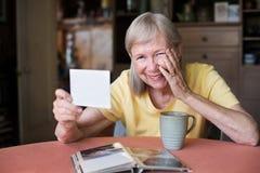 Skratta kvinnan som ser fotoet royaltyfri foto
