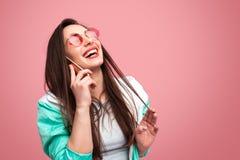Skratta kvinnan som talar på telefonen arkivfoto