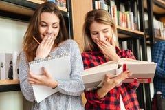 Skratta läseboken för två studenter för unga damer Royaltyfri Fotografi