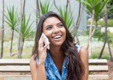 Skratta latin - den amerikanska kvinnan i jeans klår upp på telefonen Arkivbild