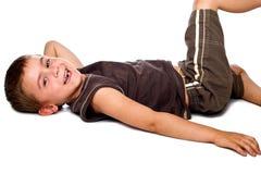 skratta liggande barn för pojkejordning Arkivbild