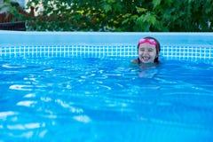 Skratta lilla flickan i en simbassäng Fotografering för Bildbyråer