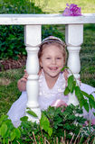 Skratta lilla flickan i en trädgård Arkivbilder