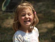 Skratta lilla flickan med blont hår royaltyfria foton
