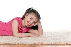 Skratta lilla flickan på den vita mattan fotografering för bildbyråer