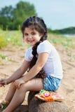 Skratta lilla flickan som poserar sammanträde på journal Royaltyfri Foto