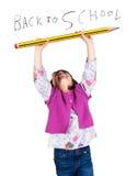 Skratta lilla flickan som rymmer en stor blyertspenna Arkivfoton