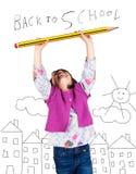 Skratta lilla flickan som rymmer en stor blyertspenna royaltyfri fotografi
