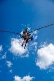Skratta liten flickabanhoppning med gummibandet och trampolinen i himlen arkivfoton