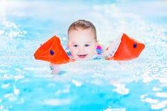 Skratta litet barnflickan som har gyckel i simbassäng Arkivbild
