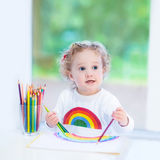 Skratta litet barnflickateckningen bredvid fönster Royaltyfria Foton