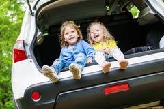 Skratta litet barnflickor som sitter i bilen Arkivbild
